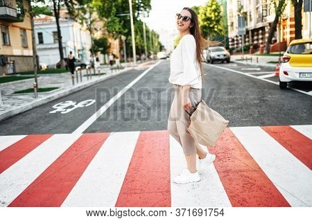 Walk Around The City. Beautiful Young Woman Is Walking On A Pedestrian Crossing With A Paper Shoppin