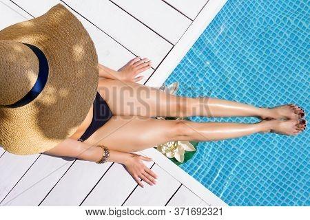 Top View Female Slim Legs. Stylish Woman Is Relaxing, Sunbathing, Sitting On Edge Of Pool. Fashionab