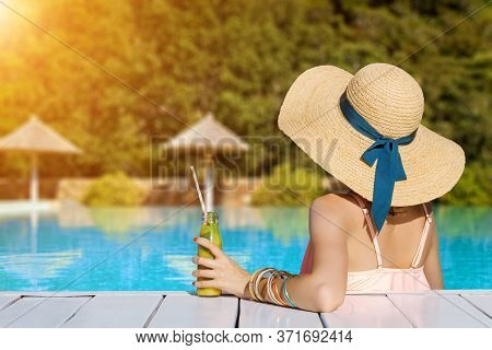 Back View Of Stylish Woman Is Relaxing, Sunbathing, Sitting In Swimming Pool. Fashionable Girl In Sw