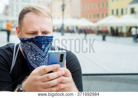Adult Man In Bandana As A Face Mask Uses Smartphone In City Cafe Terrace. Solo Outdoor Activities. S