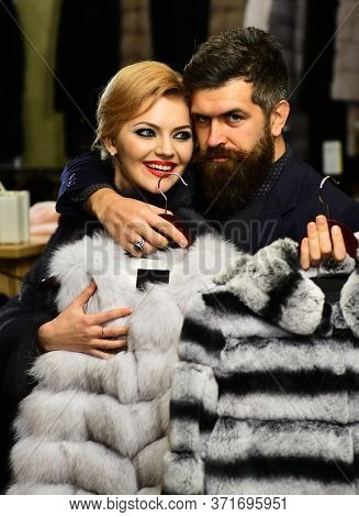 Fashion And Shopping. Couple In Love Tries Expensive Sable Overcoats
