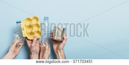 Hands Holding Recycling Rubbish Against A Blue Background