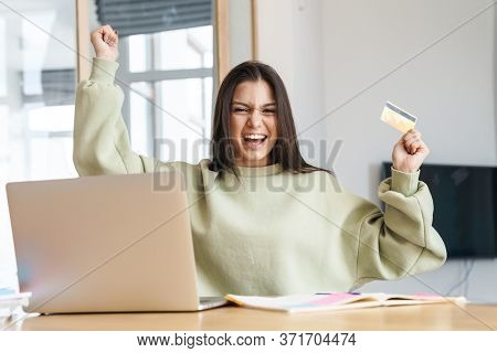 Photo of excited student woman holding credit card and making winner gesture while using laptop in living room