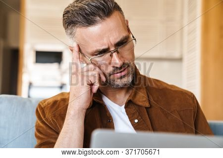 Image of perplexed adult man in eyeglasses working with laptop while sitting on couch at home