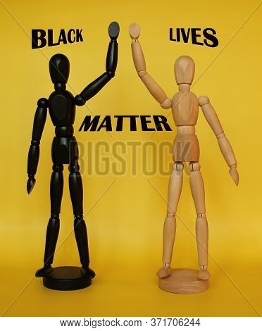 Black And White Wooden Figures On Yellow Background Stand With Their Hands Up. The Text: Black Lives