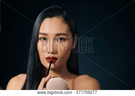Young Charming Woman Applying Lipstick Against Black Background.