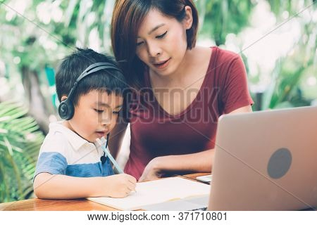 Young Asian Mother And Son Using Laptop Computer For Study And Learning Together At Home, Boy Writin