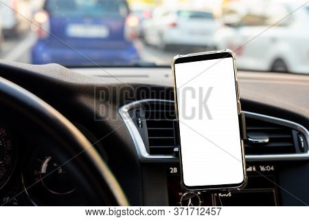 Modern Smartphone Device Gadget Mounted On Phone Holder At Car Dashboard. Mock-up White Screen Isola