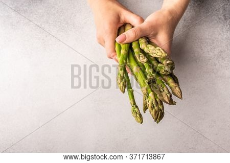 Womens Hands Hold A Bunch Of Fresh Green Asparagus Against A Light Background. Selective Focus And C