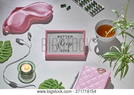 Healthy Night Sleep Creative Concept In Pink And Green. Sleep Mask, Earphones, Tea, Sleeping Pills A