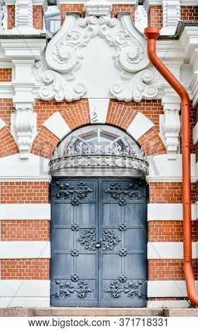 Brick Wall Of Facade Of Antique Historical Building With Stucco Moldings And Metal Door With Wrought