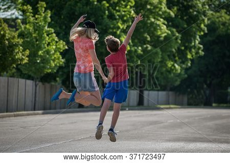 Happy Mother And Son Holding Hands While Jumping