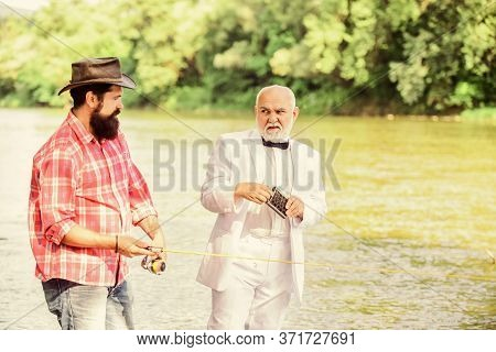 Fishing Skills. Fish With Companion Who Help In Emergency. Men Friends Relaxing River Background. Pe