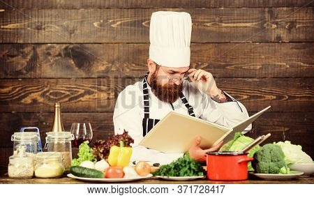 Improve Cooking Skill. Book Recipes. According To Recipe. Man Bearded Chef Cooking Food. Guy Read Bo