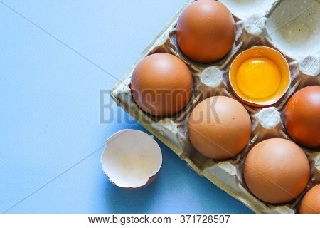 Chicken Egg Is Half Broken Among Other Eggs. Brown Eggs And Egg Yolk On The Blue Background. Top Vie