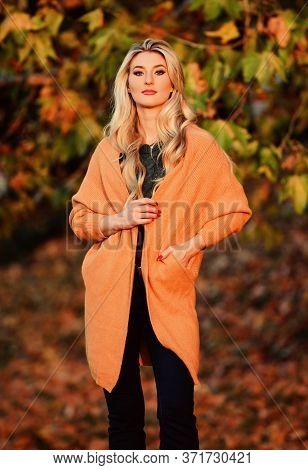 Girl Adorable Blonde Posing In Warm And Cozy Outfit Autumn Nature Background Defocused. Woman Walk S