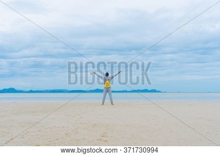 A Man Walks Along The Beach In Seclusion From Everyone, Keeping A Safe Distance, A Yellow Backpack W