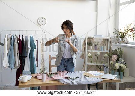 Caucasian Female Designer Photograph Clothes On Smartphone