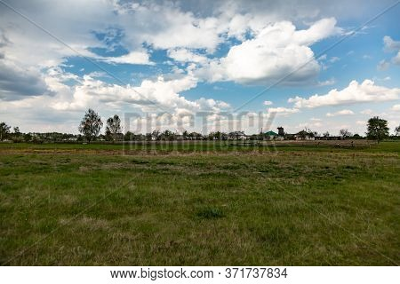 A Sky With Cumulus Clouds Over An Uncultivated Field In The Countryside. Horizontal Orientation.