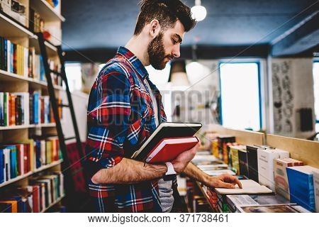 Happy Successful Hipster Guy Picking Literature And Making Research In Bookstore