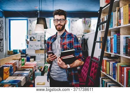 Positive Young Man Using Free 4g Internet On Cellular In Library