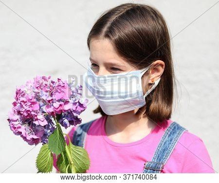 Pensive Little Girl With Surgical Mask For Protection Against Covid-19 And Has Hydrangea Flowers