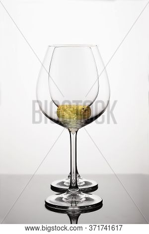 Two Empty Wineglasses On Diffision With Yellow Cork Inside Is On A Table In A White Background. Abst