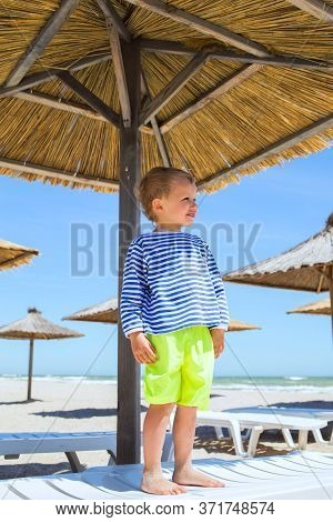 One Smiling Little Boy Stay And Pose At Chaise Lounge Deck Chair Under Straw Wooden Umbrella At Sea