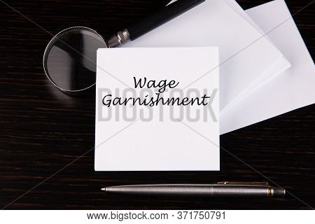 Conceptual Hand Writing Wage Garnishment Message On A White Sticker With Pen On A Black Table.