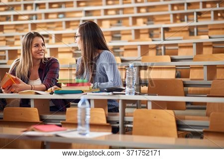 Young female colleagues talking and smiling together in amphitheater