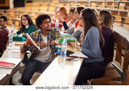 Young college students branstorming and comparing notes in amphitheater