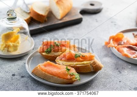 Bruschetta With Smoked Salmon And Butter On Concrete Table With Bread, Butter And Herbs. Delicious S