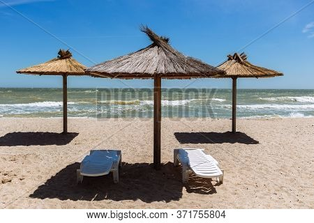 White Plastic Chaise Longues And Eco Straw And Wooden Umbrellas Parasol At Empty Beach, Ukrainian Re