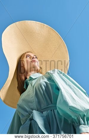 Beautiful young woman in light elegant summer dress and a wide brim hat against the blue sky. Fashion shot, summer style.