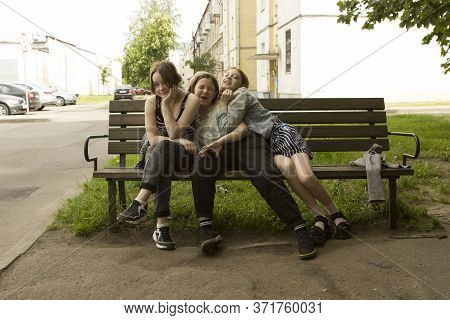 Three fashionable teenager girl friends sitting laughing. smiling and hugging on a bench near the entrance of the house. Joyful meeting after quarantine. Minsk, Belarus. 06/07/2020