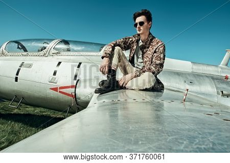 Handsome man pilot wearing military uniform sits on the wing of a fighter airplane at the airfield. Military aircraft.