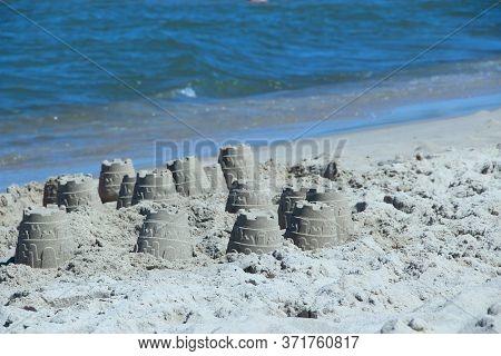 Sandy Pyramid On The Seashore. Sand Pyramid Built On The Seaside. Childish Works. Sand Houses Built