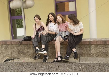 A group of four fashionable teenager friend girls sitting, laughing, smiling and hugging on the street. Happy meeting after quarantine cancellation. Minsk, Belarus. 06/07/2020
