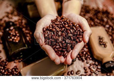 Roasted Coffee Beans In Female Hands, Background. Horizontal Orientation. Fresh Aromatic Dark Coffee