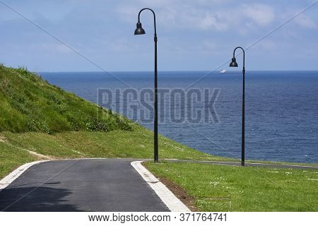 Park Detail With Cold Colours, Streetlights, Sky, Sea And Sunlight.
