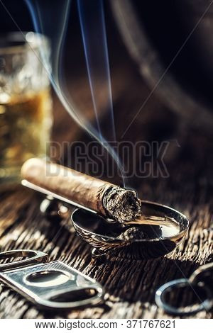 Burning Cigar With Cutter And A Glass Of Whiskey In The Back With Blueish Smoke Rising.