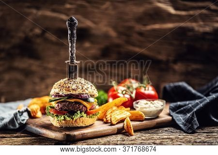 Knife Stabbed In A Hamburger With Potato Wedges On A Side In A Dark Rustic Environment.