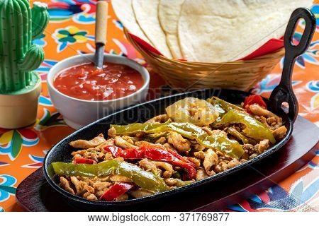 Close Up Mexican Fajita Dish. Spicy Grilled Chicken With Red And Green Bell Peppers And Hot Tomato S