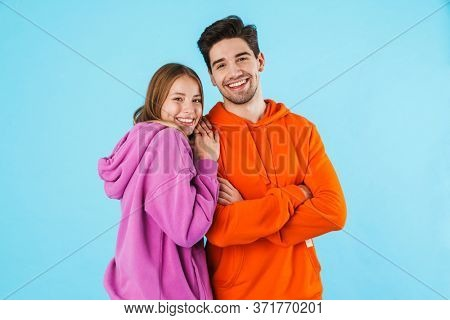 Image of positive happy loving couple isolated over blue wall background.