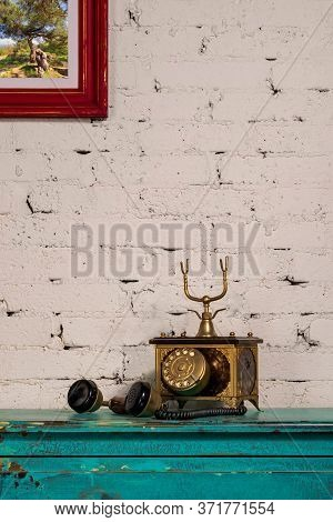 Retro Composition Of Golden Antique Telephone Set On Top Of Green Vintage Wooden Table And Backgroun