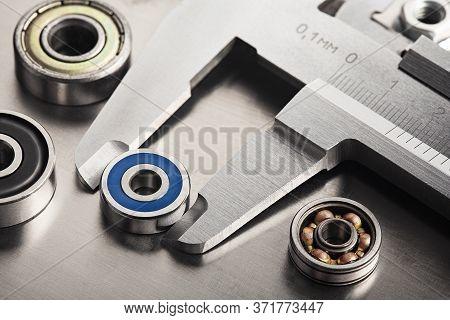 Vernier Caliper Measures Bearings Against A Metal Background. Part Of The Mechanism.