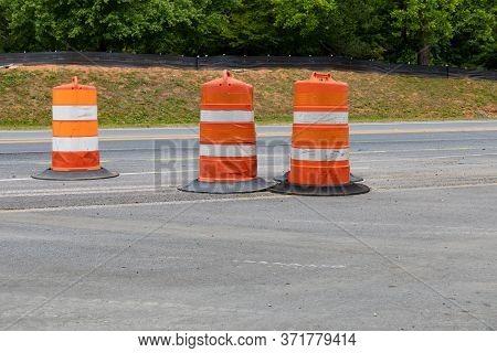 Three Traffic Barrels In A Road Construction Area, Orange Safety Barricade, Asphalt Copy Space, Hori