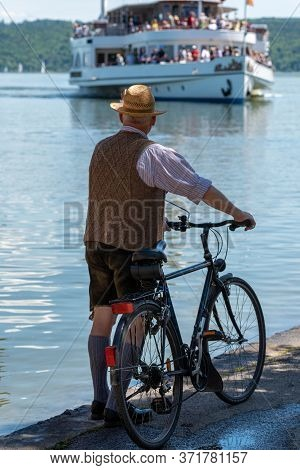 Male Dressed With Lederhose At The Dießen Harbor Looking On A Ship