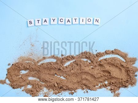Beach Sand On A Blue Background With Wood Letters And A Word Staycation