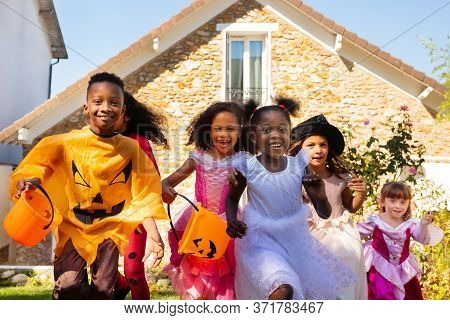 Close Portrait Of A Group Of Children Run In Halloween Costume On The Lawn In Front Of The House Tog